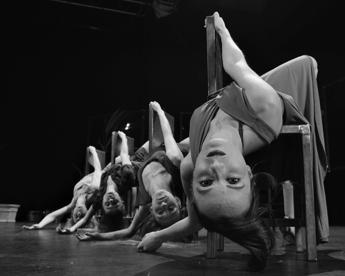 cztery kobiety wygięte na krzesłach na scenie teatralnej