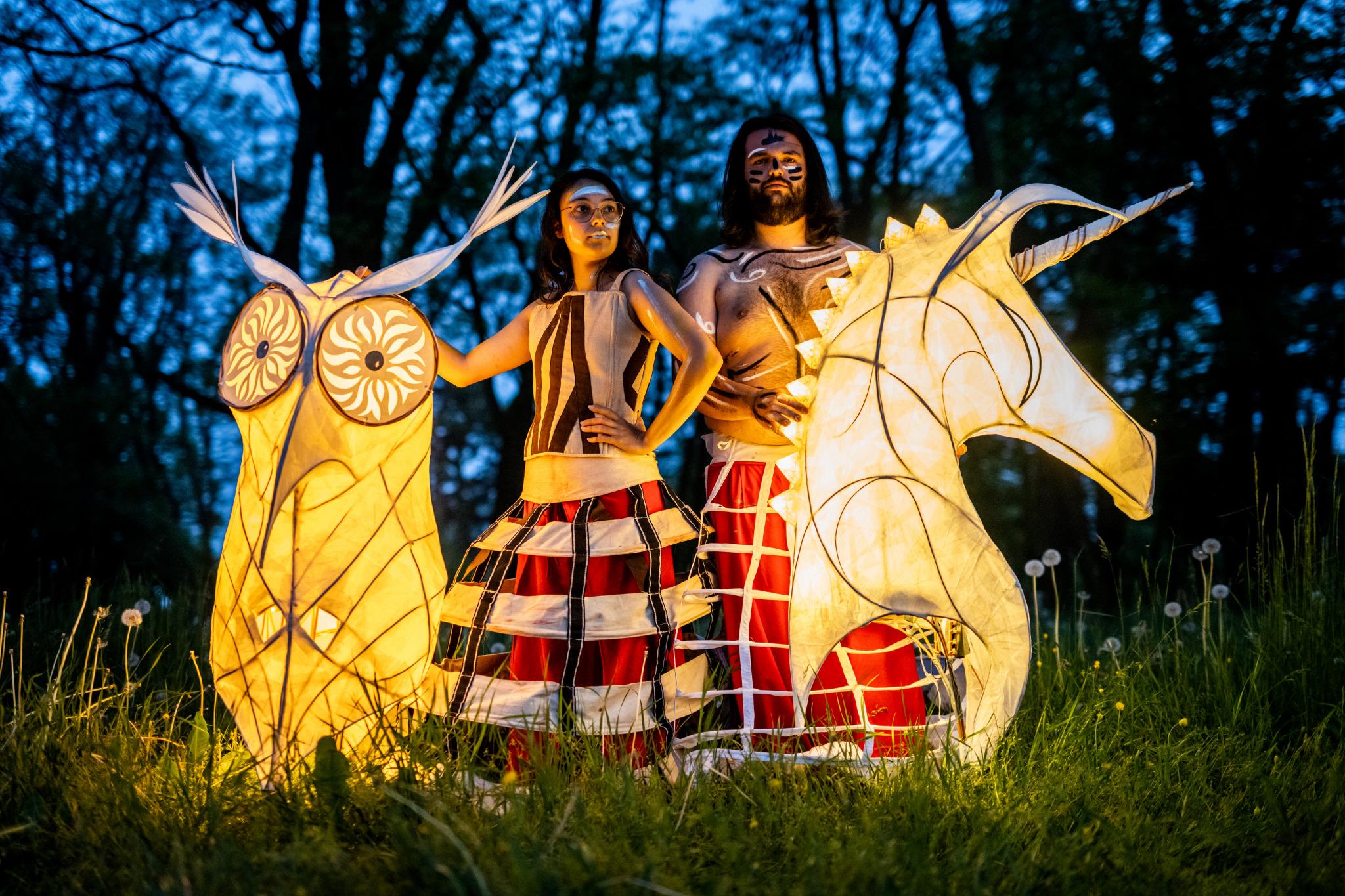 kobieta i mężczyzna trzymają lampiony teatralne w postaci sowy i jednorożca
