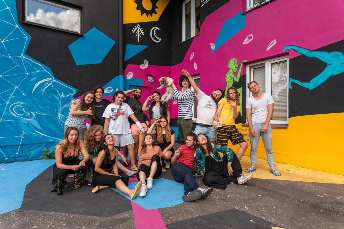 grupa wolontariuszy na tle kolorowej ściany Hajnówki Centralnej